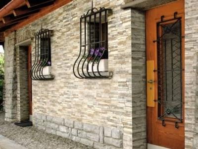 Фасад здания на фото отделан бетонной плиткой разного формата