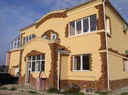 Любительское фото здания с комбинированной отделкой фасада, где используется камень и шпатлевка