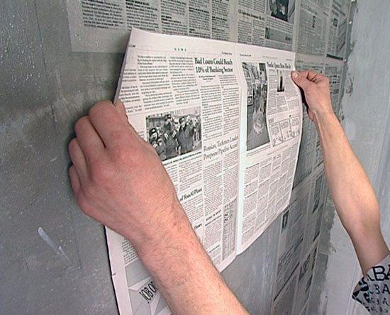 На фото – наклеивание газеты на стену