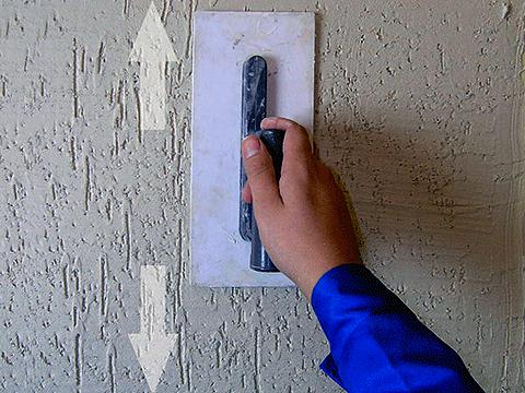 Наносим на стену штукатурку и формируем узор.