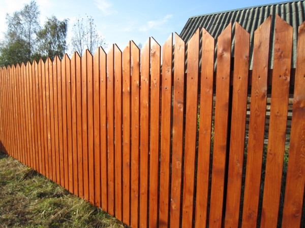 Покрытый лессирующей краской забор из штакетника