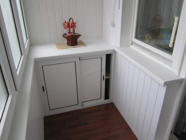 ПВХ панели и шкафчик со сдвижными створками в интерьере балкона