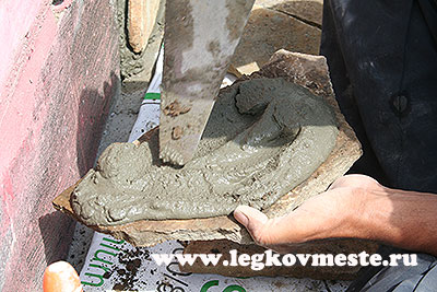 Распределите раствор по куску камня, затем прижмите его к стене.