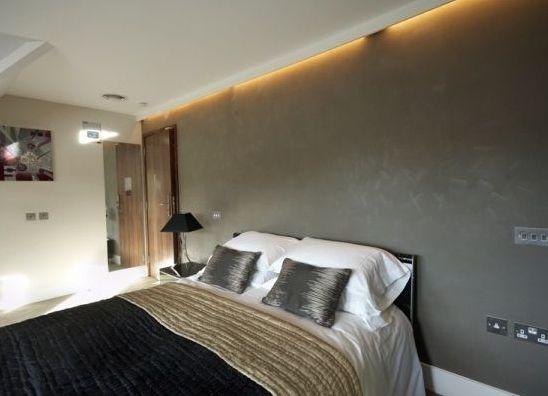 Декорирование акцентной стены в спальне цементной штукатуркой
