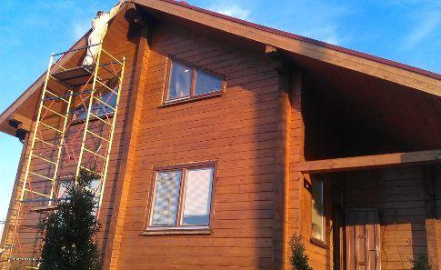 Дом из бруса окрашен масляной краской темного цвета.