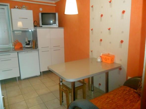 Фото реальной кухни с фартуком из МДФ и обоями. Стена у стола покрыта бесцветным акриловым лаком для дополнительной защиты