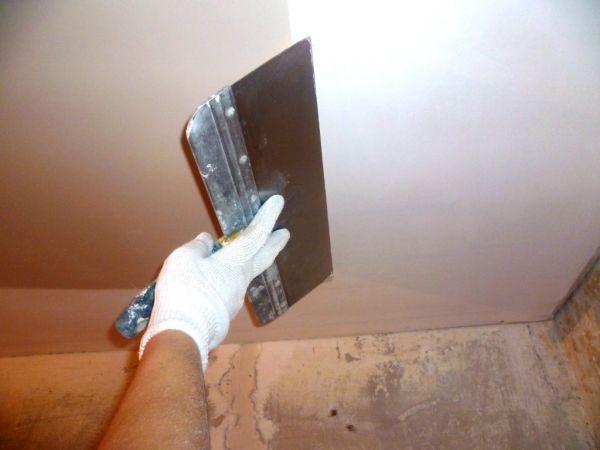 Использование широкого шпателя для шпаклевания потолка