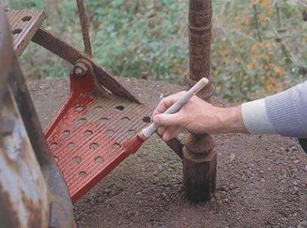 Любительское фото, процесса нанесения грунтовки на металлическую ржавую поверхность