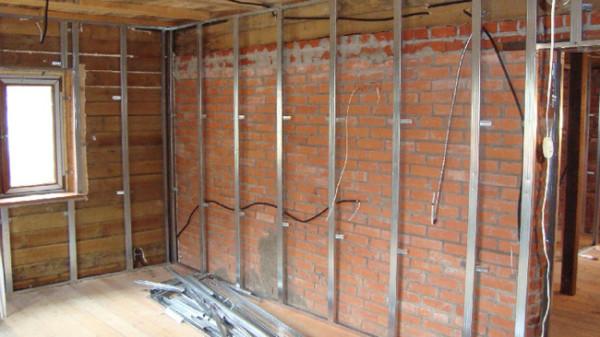 Металлический профиль для фиксации плит гипсокартона, закрепленный и на деревянных, и на кирпичных стенах
