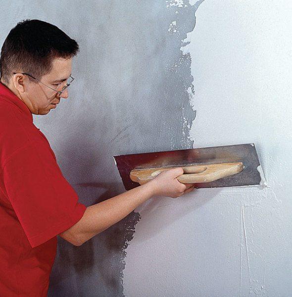 На фото - нанесение шпаклевки на стены