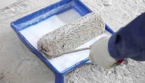 На фото - окунание валика в грунтовочный состав