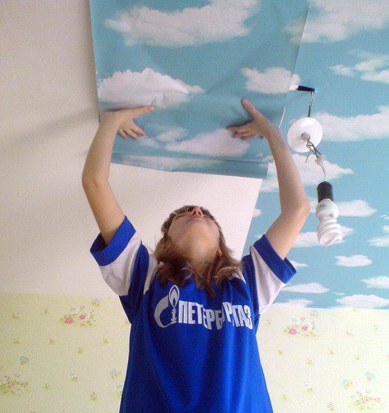 На фото - процесс оклеивания потолка
