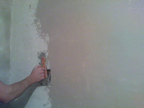 На фото - шпатлевание стены
