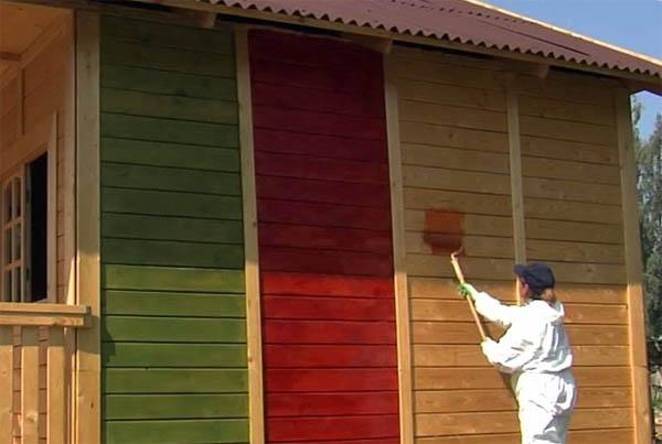 На фото – окрашивание деревянного дома снаружи валиком