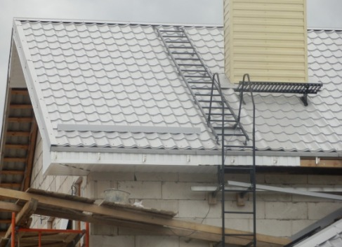 На фото – прекрасный пример настоящей заботы о будущем своей крыши – и лестницы, и спасительные уступы, и решетка перед трубой, и отделка дымохода