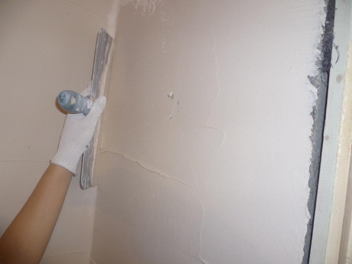 На фото – шпатлевание стены