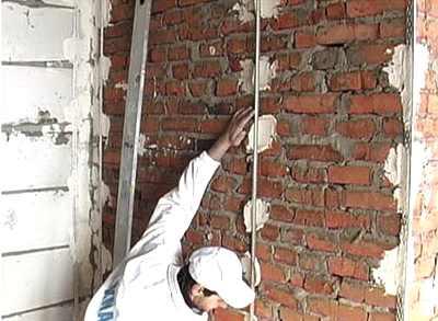 На фото монтаж маяков на кирпичную стену