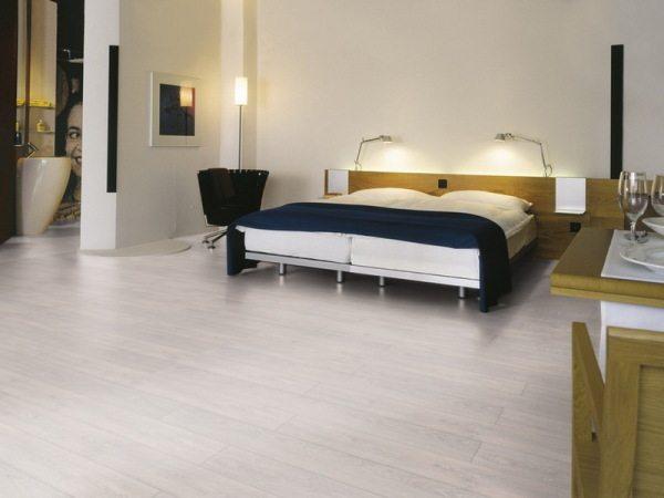 На фото неудачное оформление спальни – из-за чересчур светлого пола и стен помещение кажется слишком просторным и неуютным