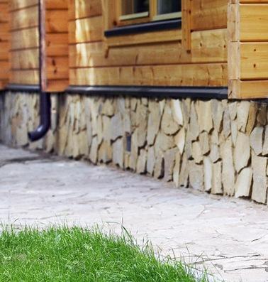 На фото: отделка натуральным камнем очень подходит для бревенчатых домов