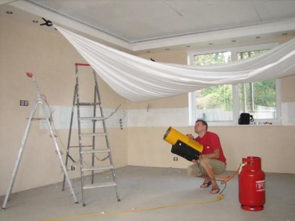 На фото показан монтаж натяжного потолка.