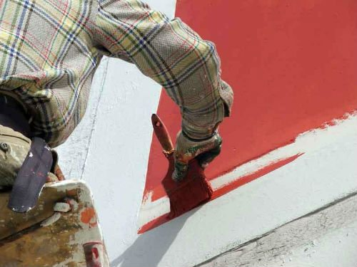 На фото показан процесс покраски оштукатуренного фасада.