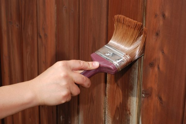 На фото показана обработка деревянного ограждения тонированной пропиткой.