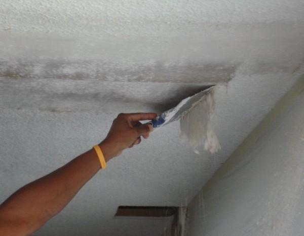 На фото показано удаление размягченной водоэмульсионной краски с потолка.