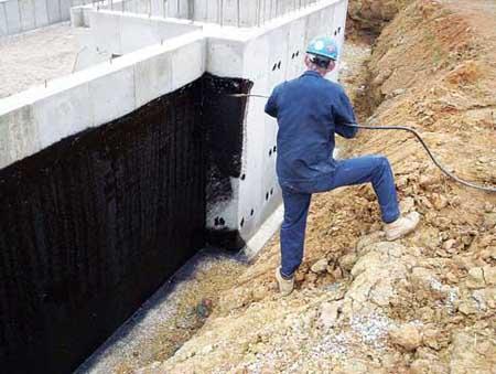 Нанесение битумной гидроизоляции с помощью распылителя