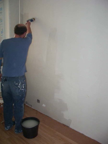 Нанесение клея макловицей на стену