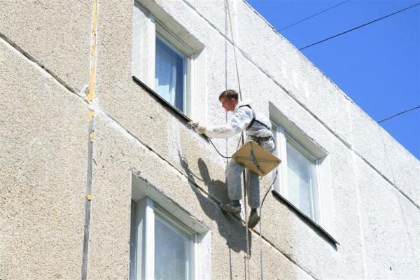 Нанесение на фасад при помощи пневматического распылителя.