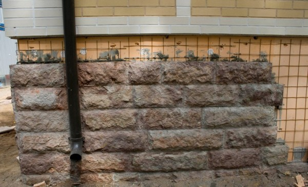 Наружная облицовка цоколя искусственным рваным гранитом.