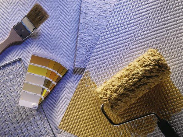 Образцы флизелиновых обоев вместе с необходимыми для покраски инструментами