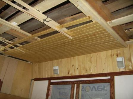 Обшивка подвесного потолка деревянной отделкой.