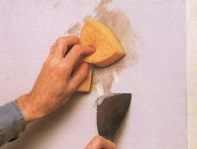 Очистка стены с помощью шпателя и губки