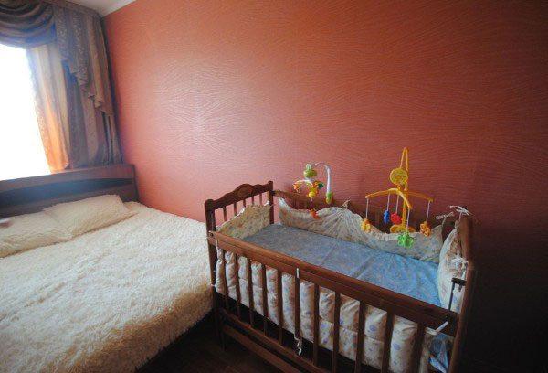 Однотонный спокойный оттенок облицовки возле детской кроватки