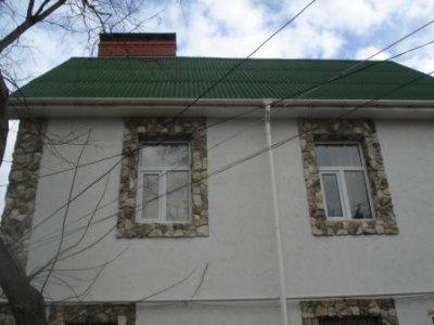 Окна на этом фото декорированы искусственным камнем