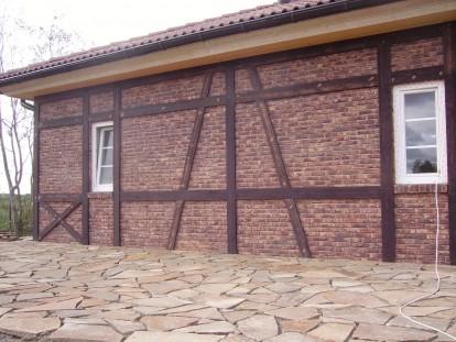 Отделка каменного дома в стиле фахверк деревянными досками.