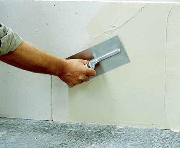Отделка стены серой цементной шпаклевкой.