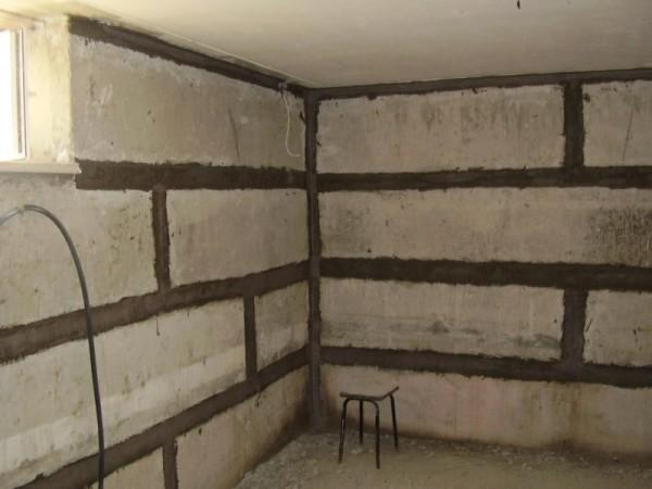 Первоначально нужно заделать все стыки и трещины на поверхности стен