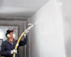 Процесс нанесения жидкой шпатлевки при помощи краскопульта.