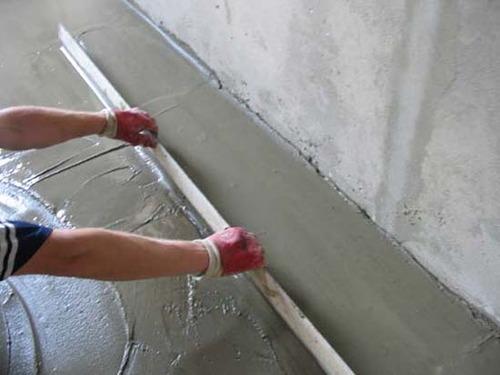 Процесс разравнивания цементно-песчаной смеси.