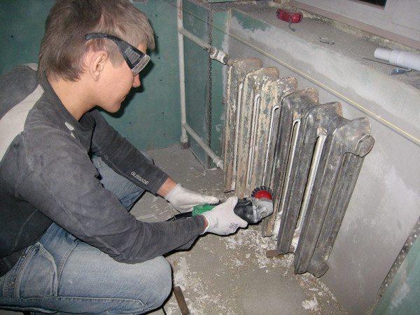 Процесс удаления старой краски с радиатора отопления.