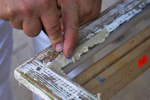 Решение вопроса, как шпаклевать окна, обязательно начинается с удаления старой шпаклевки и краски