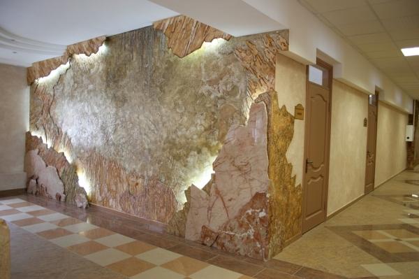 Стена на фото представляет собой оформленную венецианской штукатуркой конструкцию из гипсокартона.