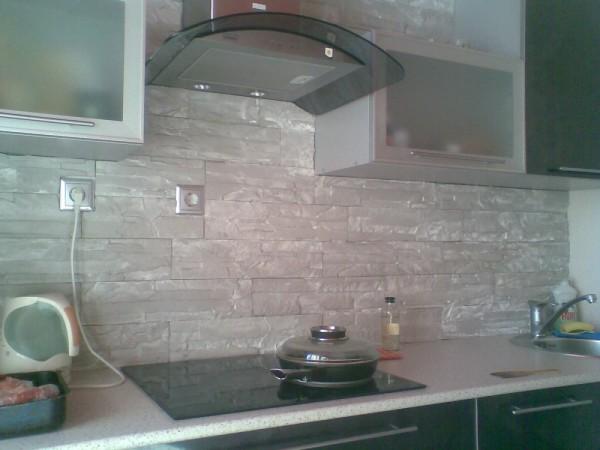 Стена в кухне облицована гипсовым камнем.