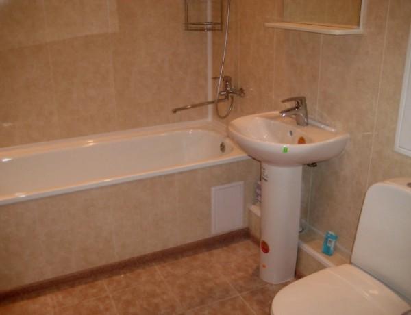 Стены в ванной отделаны ПВХ панелями