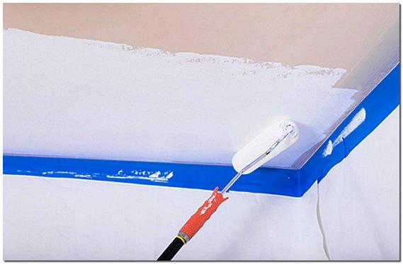 Защита стен при помощи малярного скотча и пленки позволит избежать окрашивания ненужных поверхностей