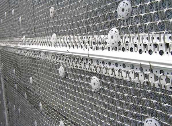 Здесь сетка закреплена дюбель-шурупами с пластиковыми шайбами.